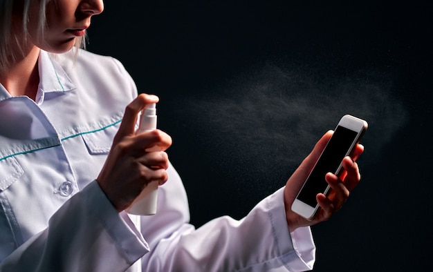 Médico desinfetando um telefone com desinfetante