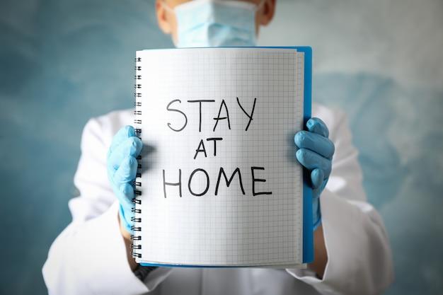 Médico detém notebook com inscrição ficar em casa na superfície azul