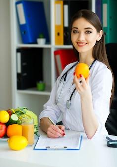 Médico dietologist detém nas mãos frescas de laranja.