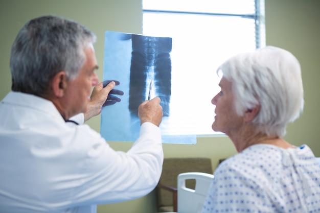 Médico discutindo relatório de raio-x com paciente sênior