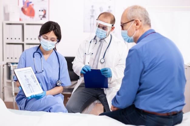 Médico discutindo sobre doença óssea com homem sênior apontando para tablet pc em cardiologia usando máscara facial na época de covid 19