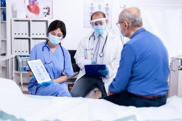 Médico dizendo a um idoso que ele está sofrendo de osteoporose durante o exame médico em um quarto de hospital usando máscara protetora contra covid-19