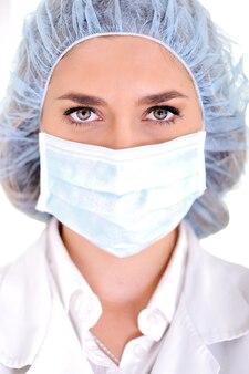 Médico do sexo feminino com tampa e máscara cirúrgicas