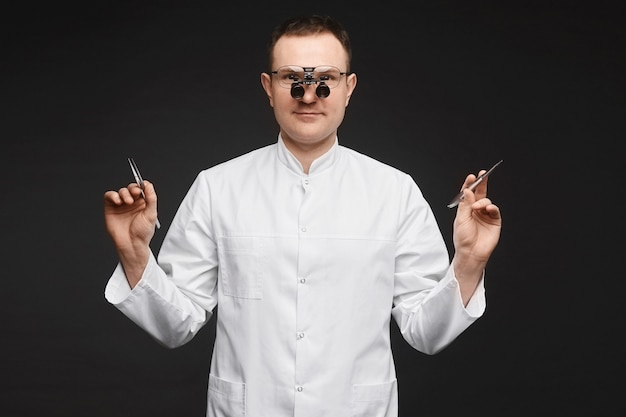 Médico do sexo masculino, caucasiano, em óculos de lupas binoculares e com equipamento de cirurgião em fundo preto.