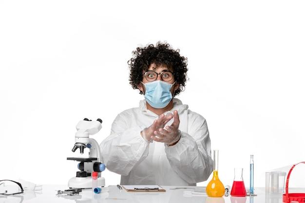 Médico do sexo masculino de frente para o terno de proteção e máscara batendo palmas sobre o vírus covid de fundo branco - pandemia de saúde
