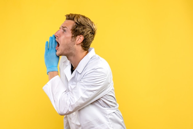 Médico do sexo masculino de vista frontal chamando alto em covida de fundo amarelo - médico de emoções humanas
