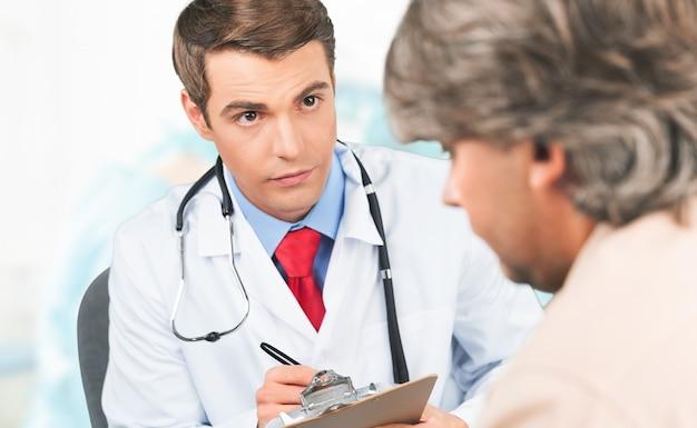 Médico do sexo masculino prescrevendo medicamentos para o paciente em segundo plano