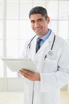 Médico do sexo masculino sorrindo com comprimido digital