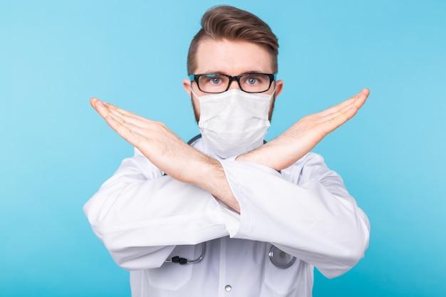 Médico do sexo masculino usa máscara levantando a mão para mostrar a parada
