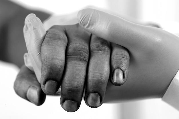 Médico do sexo masculino usando luvas azuis aperta as mãos para encorajar os pacientes