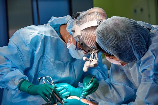 Médico e assistente de enfermeira operando para paciente de resgate de um caso de emergência perigoso. hospital e conceito de cirurgia. tratamento de câncer e doenças