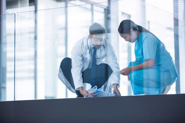 Médico e enfermeira coletando relatórios médicos caídos do chão