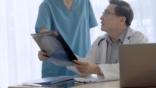 Médico e enfermeira discutem sobre o resultado da cirurgia mostrado na imagem do filme de raio-x da cabeça do paciente