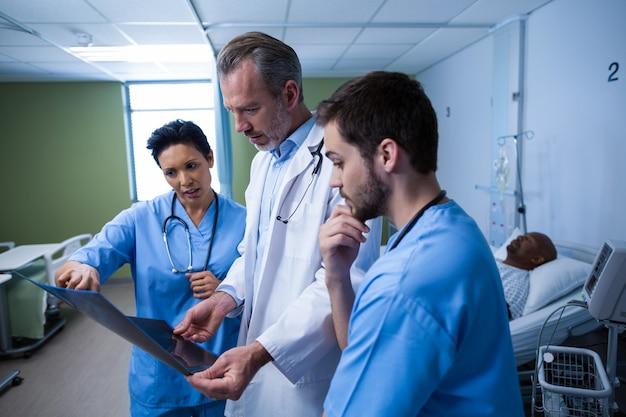 Médico e enfermeira discutindo raio-x na enfermaria