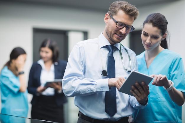 Médico e enfermeira discutindo sobre tablet digital