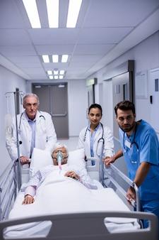 Médico e enfermeira empurrando cama de maca de emergência no corredor
