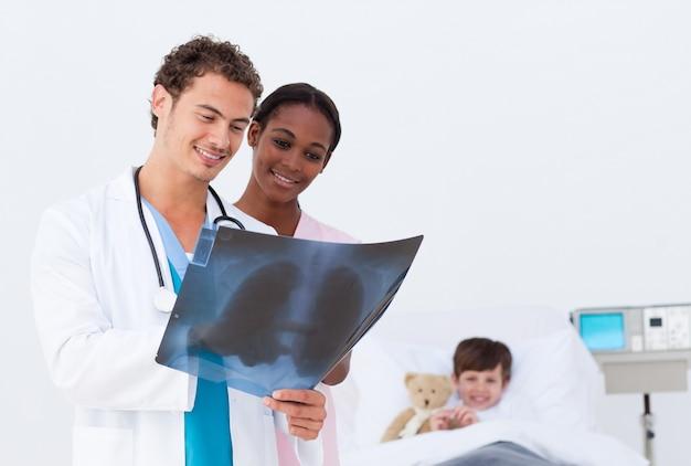 Médico e enfermeira examinando um raio-x no filho de um quarto