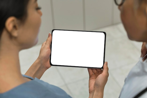 Médico e enfermeira olhando para um tablet em branco