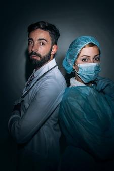 Médico e enfermeira posando nas sombras