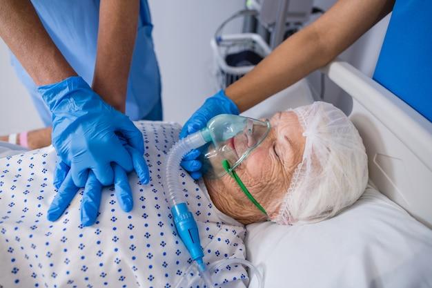 Médico e enfermeira tratando paciente sênior na enfermaria