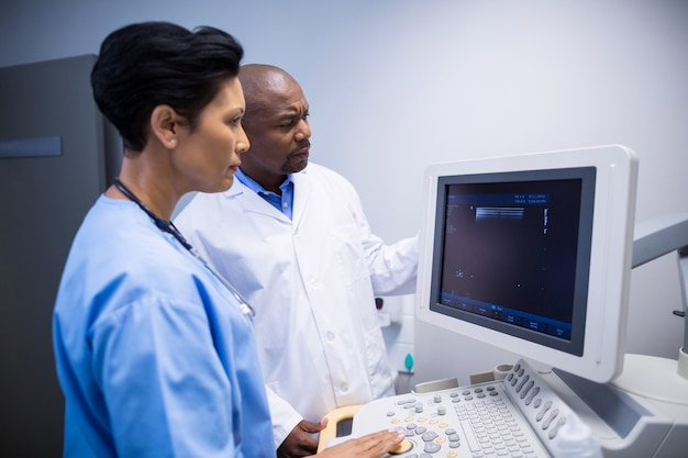 Médico e enfermeiro usando a máquina de monitoramento de pacientes na enfermaria