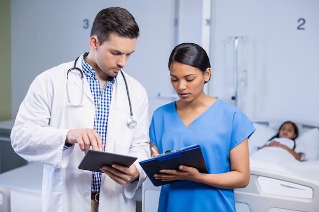 Médico e enfermeiro usando tablet digital e área de transferência