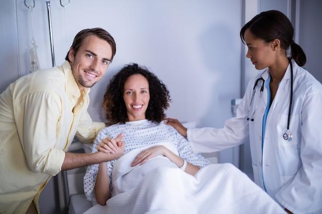 Médico e homem reconfortante mulher grávida na enfermaria