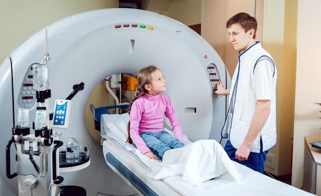 Médico e menina na sala de tomografia computadorizada
