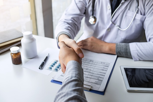 Médico e paciente apertando as mãos após um bom e bem sucedido tratamento no conceito hospitalar, de saúde e de assistência.