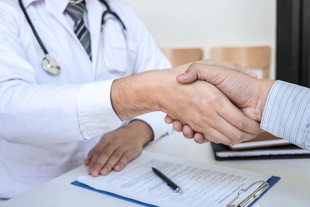 Médico e paciente apertando as mãos após um bom e bem sucedido tratamento no hospital