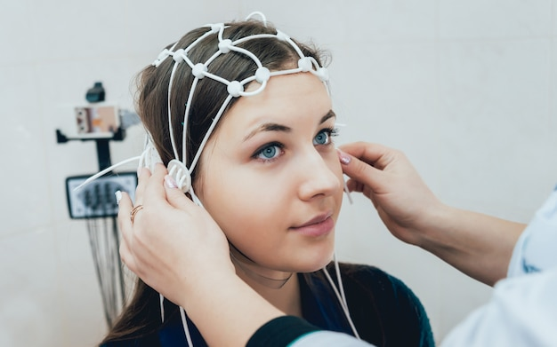 Médico e paciente com eletrodo de encefalografia.