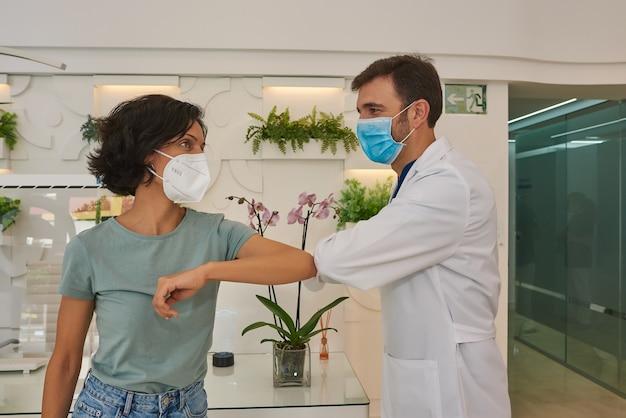 Médico e paciente cumprimentam-se batendo os cotovelos. eles usam máscaras faciais. eles estão na recepção da clínica.