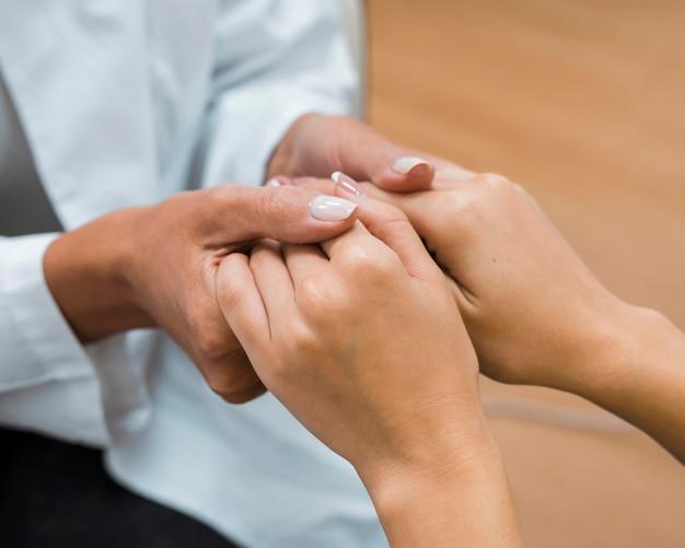 Médico e paciente de mãos dadas após close-up de boas notícias
