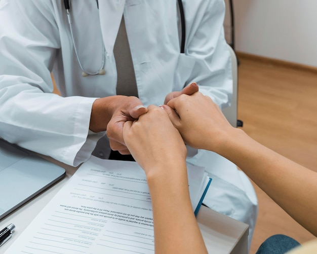 Médico e paciente de mãos dadas após close-up de más notícias