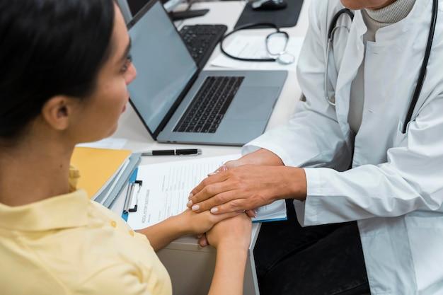 Médico e paciente de mãos dadas após más notícias