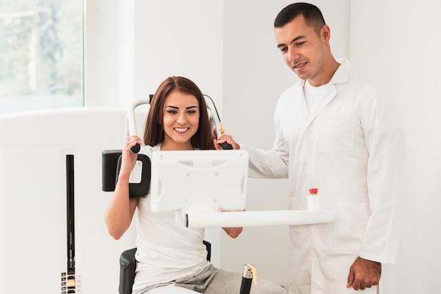 Médico e paciente do sexo feminino assistindo uma tela