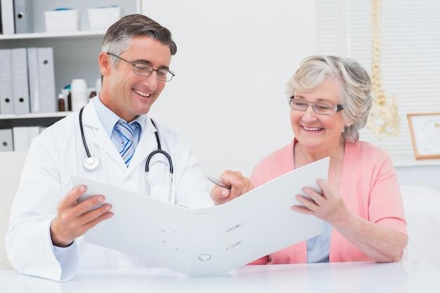 Médico e paciente do sexo feminino que olham relatórios no arquivo