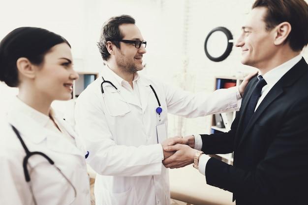 Médico e paciente é agita as mãos na clínica.