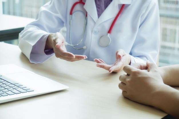 Médico e paciente estão discutindo algo, apenas as mãos na mesa