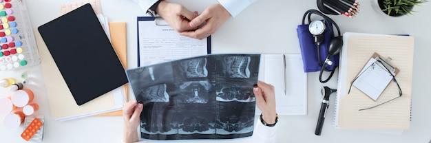 Médico e paciente estão discutindo o raio x no conceito de serviço médico de mesa de trabalho