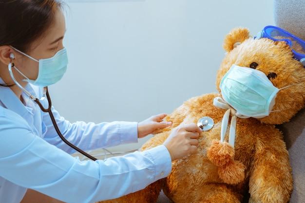 Médico e paciente, examinando a máscara usando urso marrom contra vírus e gripe. visita médica regular na clínica. conceito de medicina e saúde