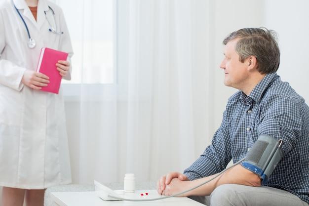 Médico e paciente, medindo o conceito de pressão arterial, saúde, hospital e medicina