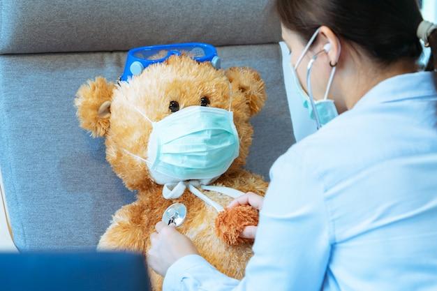Médico e paciente. medique a máscara vestindo do urso de peluche marrom contra vírus e gripe. visita médica regular na clínica. conceito de medicina e saúde