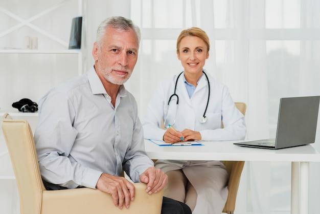 Médico e paciente, olhando para a câmera