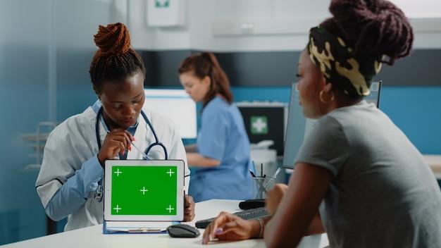 Médico e paciente olhando para a tela verde do tablet
