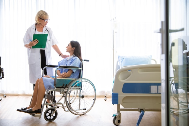Médico e paciente sorrindo, discutindo algo enquanto estão sentados à mesa