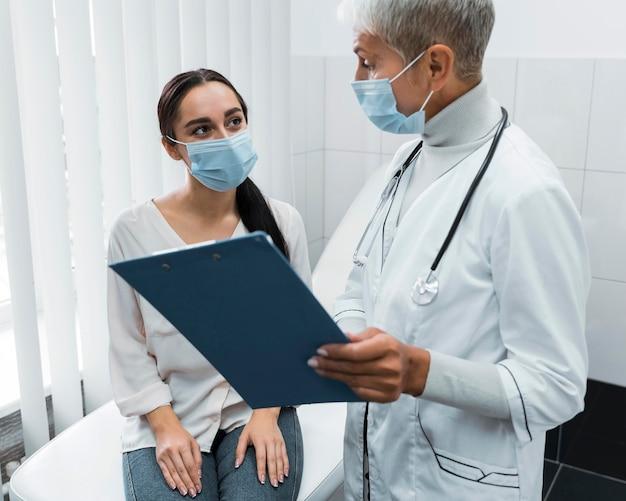 Médico e paciente usando máscaras faciais