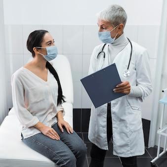 Médico e paciente usando máscaras médicas