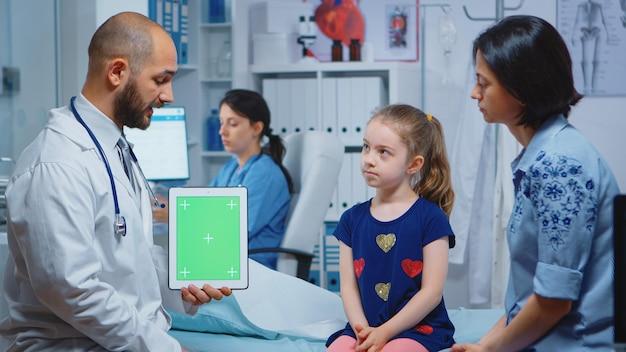 Médico e pacientes olhando para tablet de tela verde no consultório médico. especialista em saúde com tela de substituição de maquete isolada de notebook de chroma key. tema médico relacionado à medicina de keying fácil.