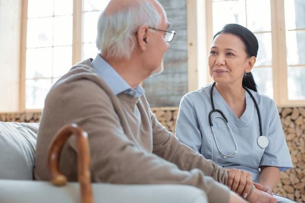 Médico em casa. bom feliz médico vestindo uniforme enquanto olha para o homem sênior que está sentado ao lado dela